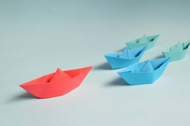 Red paperboat leading paperboats